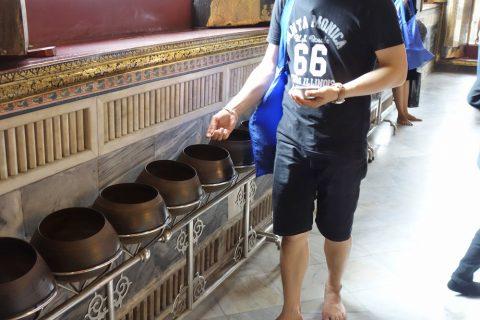 ワットポー大寝釈迦仏で壷に硬貨を入れる