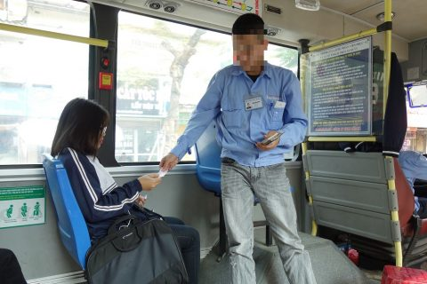 ハノイのバスの若い車掌